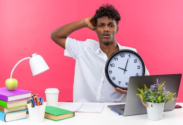 Jovem estudante afro-americano ansioso sentado na mesa com as ferramentas da escola, colocando a mão na cabeça dele e segurando o relógio