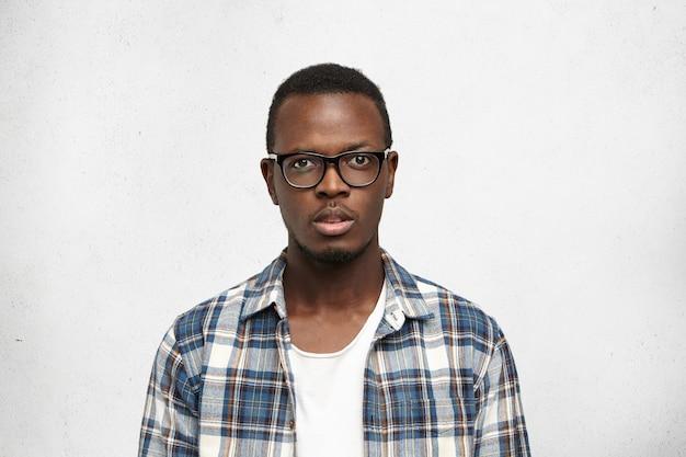 Jovem estudante afro-americano com óculos grandes e elegantes, isolado no whitee