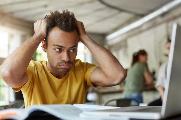 Jovem estudante afro-americano estressado, sentindo-se frustrado, sentado no espaço de coworking em frente a um laptop aberto, segurando a cabeça com as mãos