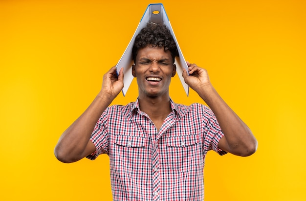 Jovem estudante afro-americano insatisfeito segurando uma pasta de arquivo na cabeça