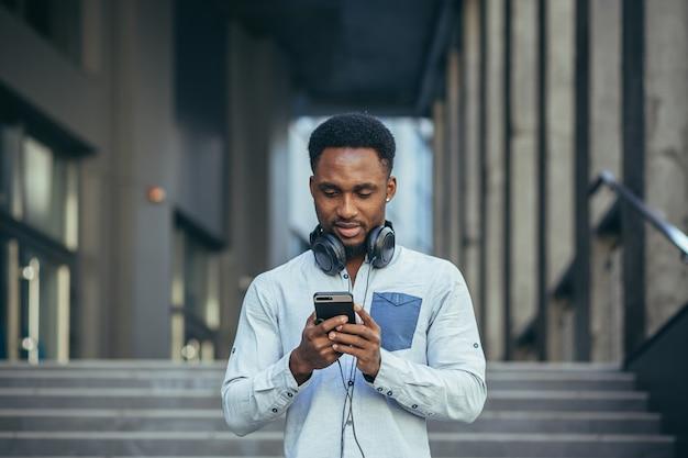 Jovem estudante afro-americano ouve podcast usando app no telefone e um grande fone de ouvido, com roupas casuais da época