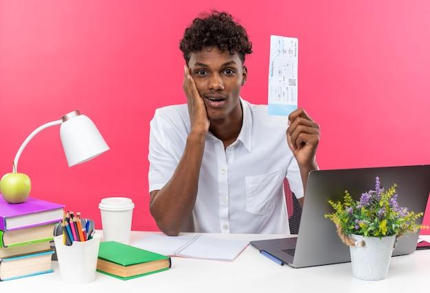 Jovem estudante afro-americano surpreso sentado na mesa com as ferramentas da escola, colocando a mão no rosto dele e segurando a passagem aérea