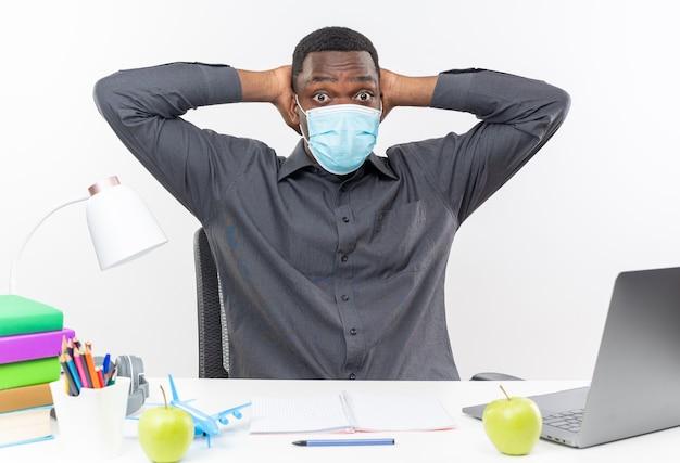 Jovem estudante afro-americano surpreso usando máscara médica, sentado na mesa com ferramentas escolares e colocando as mãos na cabeça