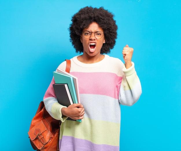 Jovem estudante afro gritando agressivamente com uma expressão de raiva ou com os punhos cerrados celebrando o sucesso