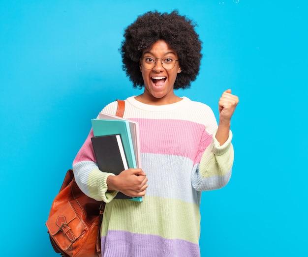 Jovem estudante afro mulher se sentindo chocada, animada e feliz, rindo e comemorando o sucesso, dizendo uau!