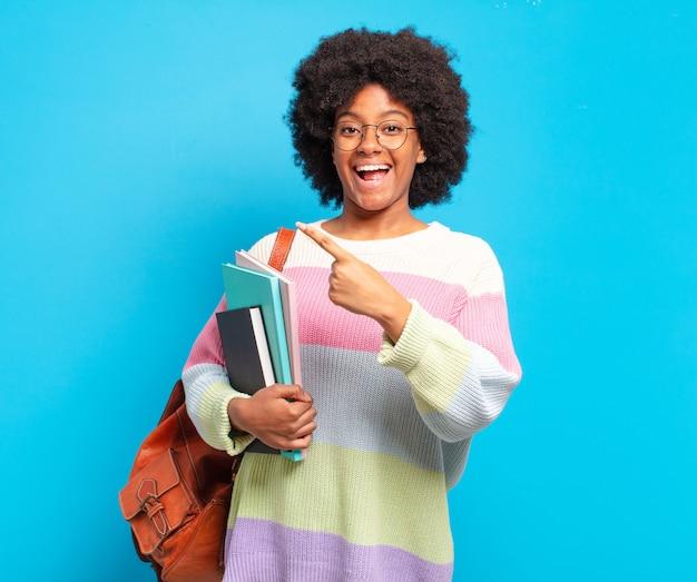 Jovem estudante afro parecendo animada e surpresa, apontando para o lado e para cima para copiar o espaço