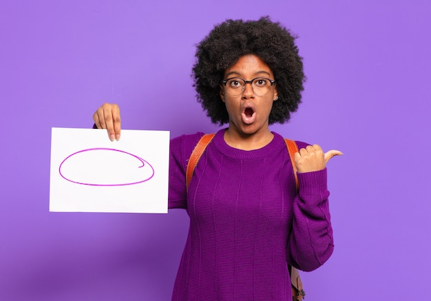 Jovem estudante afro parecendo espantada de descrença, apontando para um objeto ao lado e dizendo uau, inacreditável