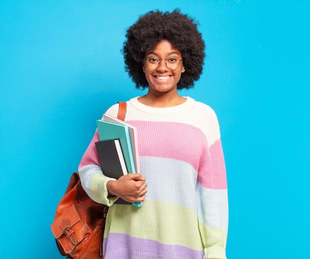 Jovem estudante afro parecendo feliz e agradavelmente surpresa, animada com uma expressão de fascínio e choque