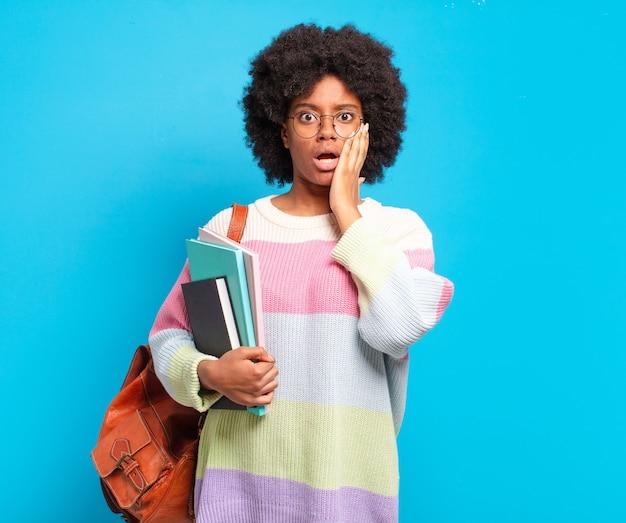 Jovem estudante afro se sentindo chocada e assustada, parecendo apavorada com a boca aberta e as mãos nas bochechas