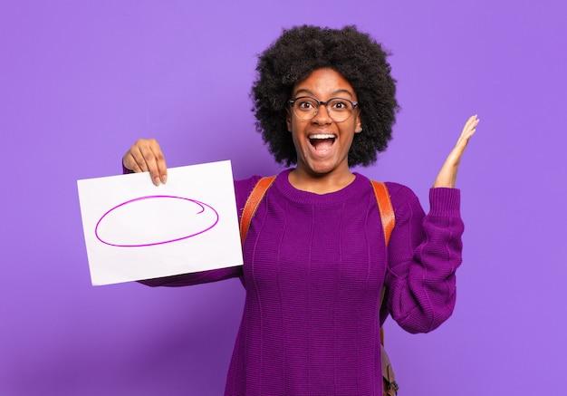 Jovem estudante afro se sentindo feliz, animada, surpresa ou chocada, sorrindo e atônita com algo inacreditável