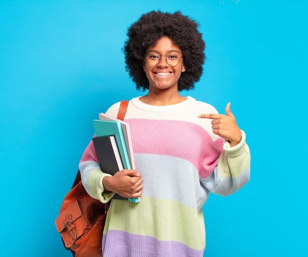 Jovem estudante afro se sentindo feliz, surpresa e orgulhosa, apontando para si mesma com um olhar animado e surpreso