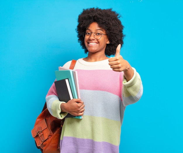 Jovem estudante afro se sentindo orgulhosa, despreocupada, confiante e feliz, sorrindo positivamente com o polegar para cima