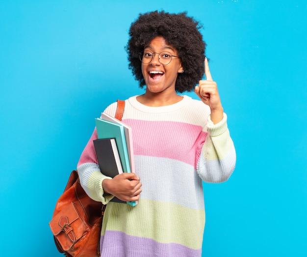 Jovem estudante afro se sentindo um gênio feliz e animado depois de realizar uma ideia, levantando alegremente o dedo, eureka!