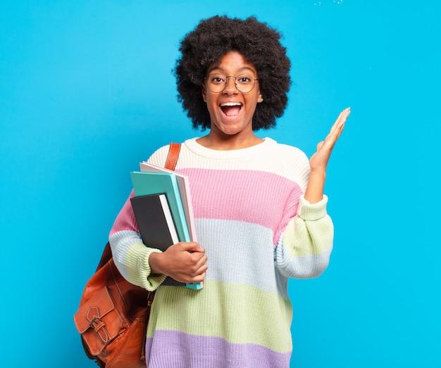Jovem estudante afro sentindo-se feliz, animada, surpresa ou chocada, sorrindo e atônita com algo inacreditável
