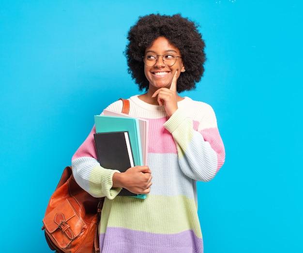 Jovem estudante afro sorrindo feliz e sonhando acordada ou duvidando, olhando para o lado