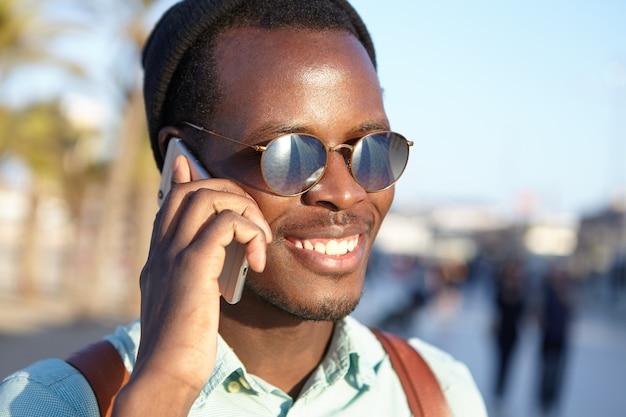 Jovem estudante alegre em óculos de sol com lentes de espelho e chapéus, sorrindo alegremente