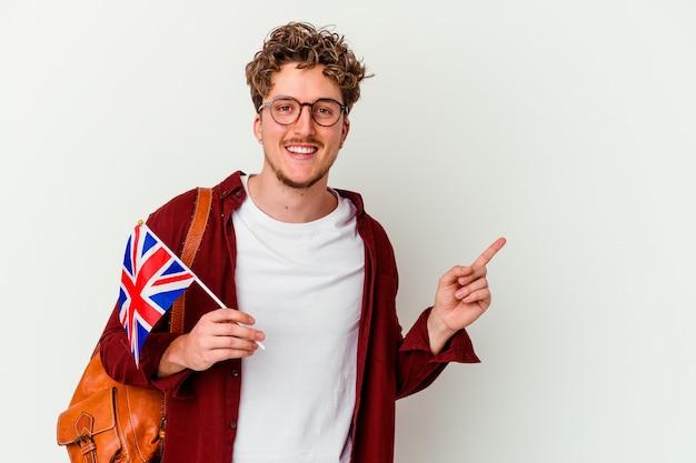 Jovem estudante aprendendo inglês isolado na parede branca, sorrindo e apontando para o lado, mostrando algo no espaço em branco