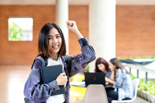 Jovem estudante asiática atraente feliz sorrindo para a câmera