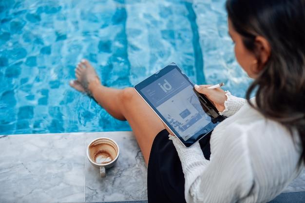 Jovem estudante asiática com tablet moderno faz algum trabalho e relaxa ao redor da piscina na mansão.