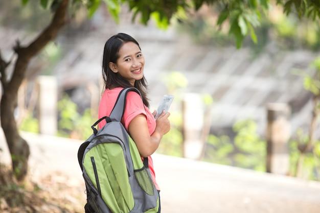 Jovem estudante asiática em pé ao ar livre, segurando um telefone celular e sm
