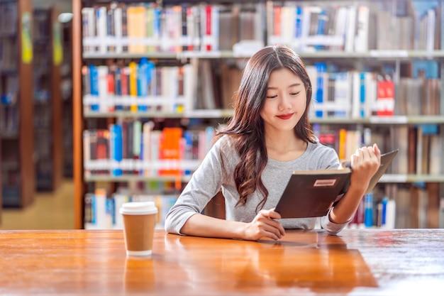 Jovem estudante asiática em terno casual, lendo o livro com uma xícara de café na biblioteca da universidade ou colega na mesa de madeira sobre a parede da estante de livros, volta ao conceito de escola