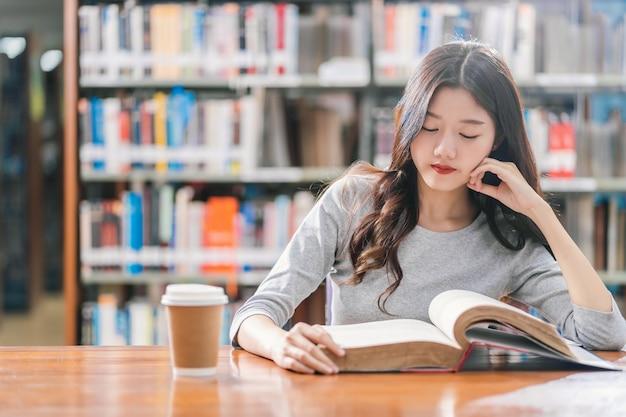 Jovem estudante asiática em traje casual, lendo o livro com uma xícara de café na biblioteca da universidade ou colega