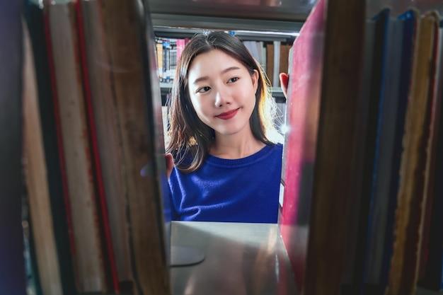 Jovem estudante asiática em traje casual, procurando o livro em sentimento de felicidade da estante de livros na biblioteca da universidade ou colega