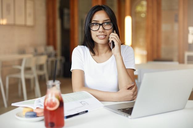 Jovem estudante asiática falando ao telefone de óculos, usando um laptop, bebendo limonada em um café claro, mas vazio