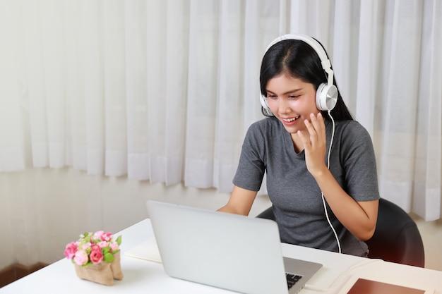 Jovem estudante asiática, inteligente e ativa, sentada à mesa com fone de ouvido, usando o computador e anotando para estudar online