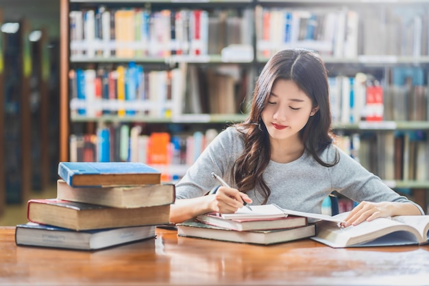 Jovem estudante asiática lendo e fazendo lição de casa na biblioteca da universidade