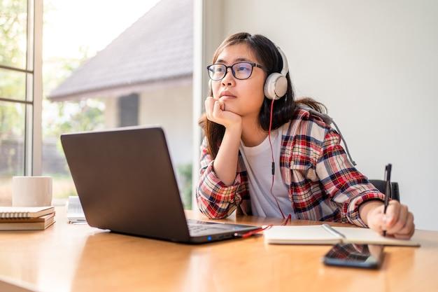 Jovem estudante asiática olhando para cima, pensando enquanto trabalhava e estudava em casa durante o bloqueio da cidade devido à propagação do vírus corona