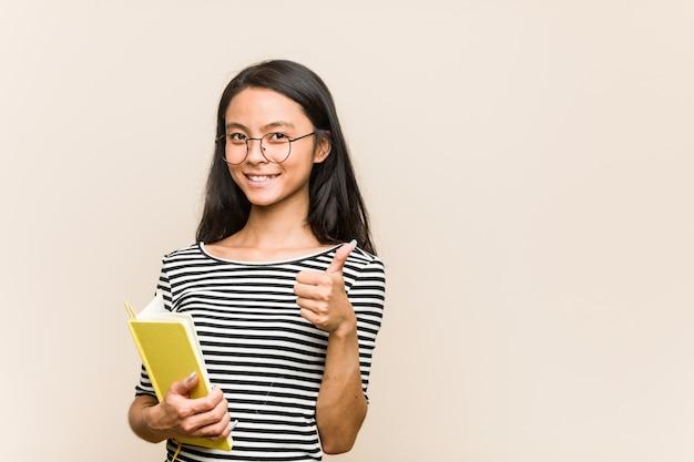 Jovem estudante asiática segurando um livro sorrindo e levantando o polegar