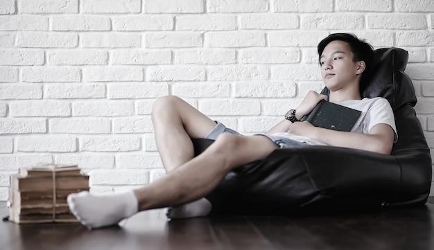 Jovem estudante asiática sentada no travesseiro e se preparando para o exame