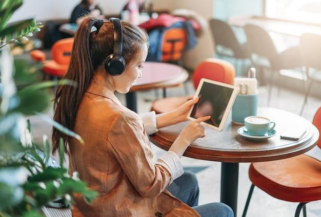 Jovem estudante asiática sorridente com fones de ouvido se comunica por tablet e aprende língua estrangeira no café