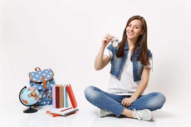 Jovem estudante atraente mulher casual em roupas jeans segurando um despertador sentado perto do globo, mochila, livros escolares isolados