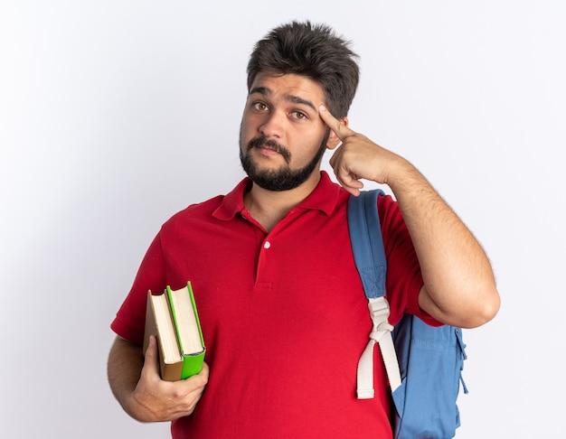 Jovem estudante barbudo com uma camisa pólo vermelha com mochila segurando notebooks apontando com o dedo indicador para sua têmpora com um sorriso no rosto inteligente em pé sobre uma parede branca