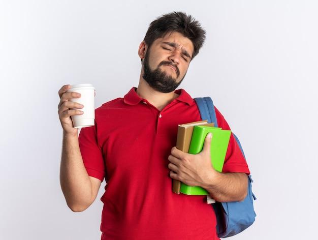 Jovem estudante barbudo com uma camisa pólo vermelha com uma mochila segurando cadernos e uma xícara parecendo descontente e confuso em pé sobre um fundo branco