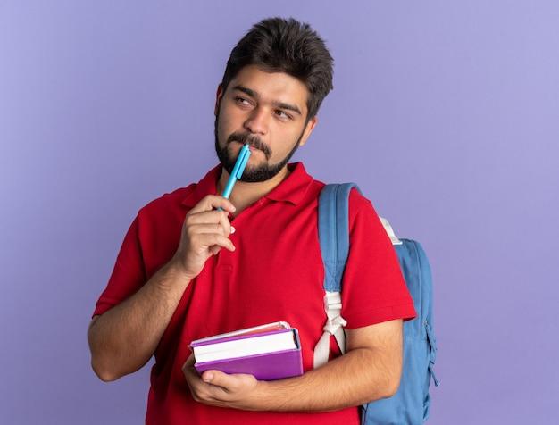 Jovem estudante barbudo com uma camisa pólo vermelha com uma mochila segurando livros e uma caneta olhando de lado perplexo em pé