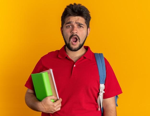 Jovem estudante barbudo com uma camisa pólo vermelha e uma mochila segurando cadernos parecendo confuso e surpreso em pé