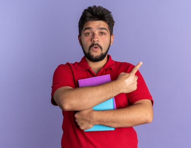 Jovem estudante barbudo com uma camisa pólo vermelha segurando livros, espantado e surpreso, apontando com o dedo indicador para o lado em pé sobre a parede azul