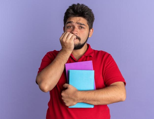 Jovem estudante barbudo com uma camisa pólo vermelha segurando livros, estressado e nervoso, roendo as unhas em pé sobre a parede azul