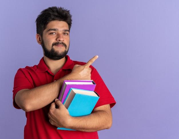 Jovem estudante barbudo com uma camisa pólo vermelha segurando livros, parecendo confiante, sorrindo apontando com o dedo indicador para o lado em pé