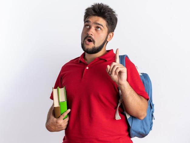 Jovem estudante barbudo em uma camisa pólo vermelha com mochila segurando cadernos olhando para cima surpreso mostrando o dedo indicador tendo uma nova ideia em pé