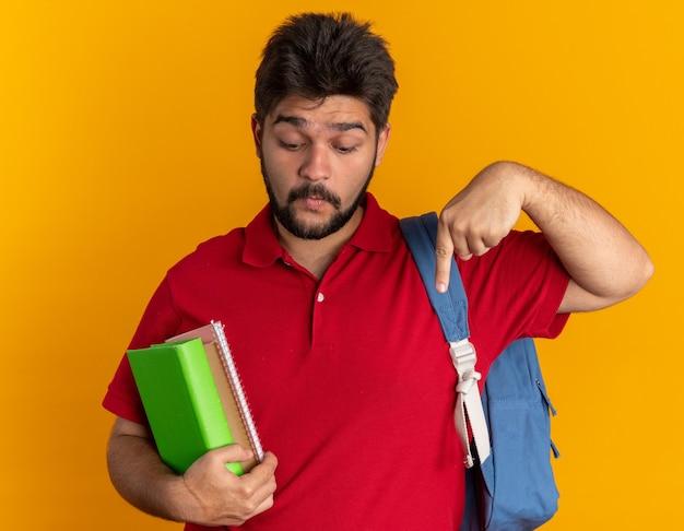 Jovem estudante barbudo em uma camisa pólo vermelha com mochila segurando cadernos parecendo surpreso apontando com o dedo indicador para baixo em pé