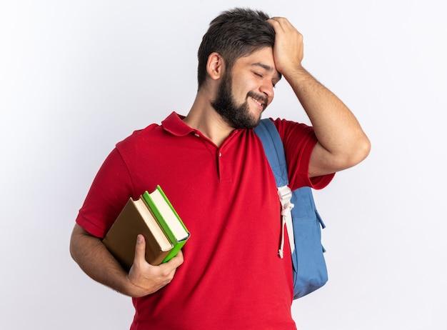 Jovem estudante barbudo em uma camisa pólo vermelha com mochila segurando cadernos sorrindo confuso com a mão na cabeça em pé
