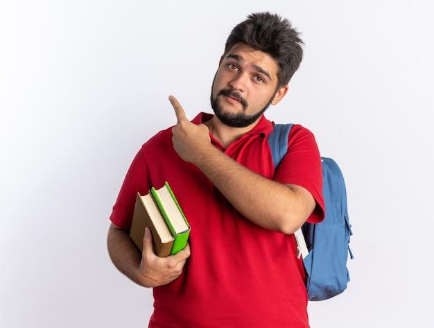 Jovem estudante barbudo em uma camisa pólo vermelha com mochila segurando notebooks lookign para a câmera feliz e positivo apontando com o dedo indicador para o lado em pé sobre um fundo branco