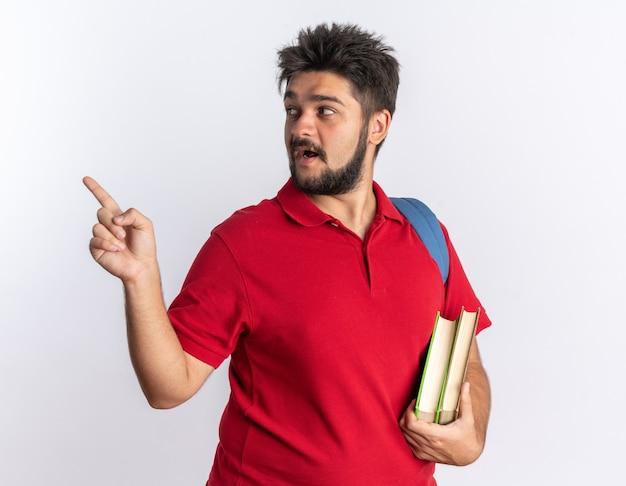 Jovem estudante barbudo em uma camisa pólo vermelha com mochila segurando notebooks olhando para o lado apontando com o dedo indicador para o lado sorrindo em pé