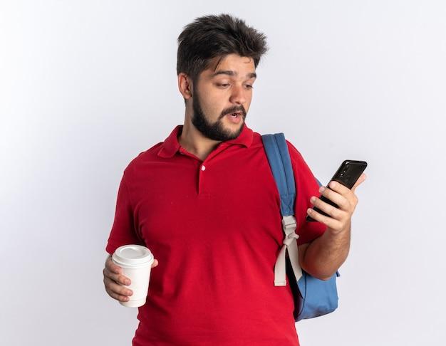 Jovem estudante barbudo em uma camisa pólo vermelha com uma mochila segurando um smartphone e uma xícara de café parecendo confuso em pé