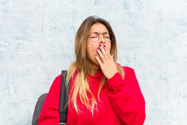 Jovem estudante bonita bocejando preguiçosamente no início da manhã, acordando e parecendo sonolenta, cansada e entediada