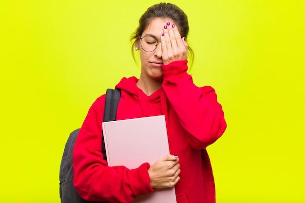 Jovem estudante bonita com sono, entediada e bocejando, com dor de cabeça e uma mão cobrindo metade do rosto